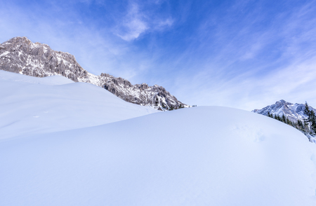 Large piles of snow - Lovely winter background with big piles of snow , surrounded by the peaks of the Austrian Alps mountains, under a blue sky.