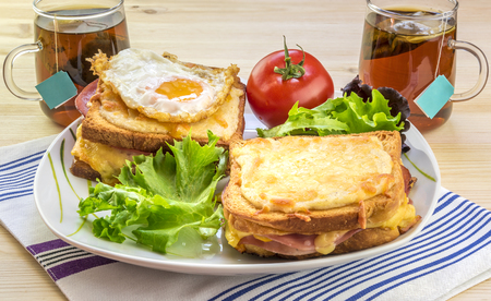 specific: French breakfast for two people - Tasty breakfast for two persons with specific french food, croque madame (with egg) and croque monsieur, seasoned with fresh salad and tea.