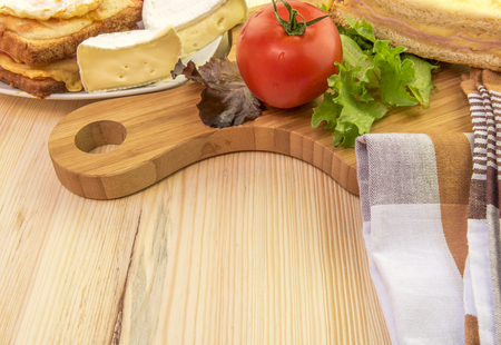 trencher: Plate and wooden platter with food - Tasty sandwiches, white cheese and some vegetables on a wooden trencher and a plate. Stock Photo