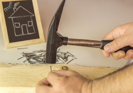 hammering: Mans hand hammering nail in wood - Image with a builders hand hammering a small nail in a wooden board and in the background a chalkboard with a funny  drawing of a house.