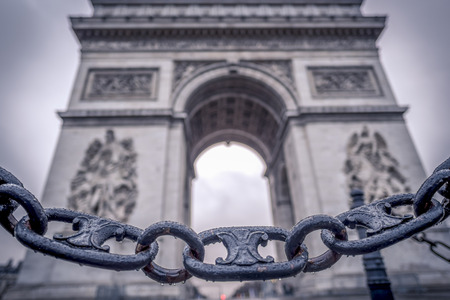 metaphoric: Chain links and the Arc de Triomphe in the background - Metaphoric image with chain links sprinkled with rain drops in the foreground and the Arc de triumph on the background, in Paris, France.