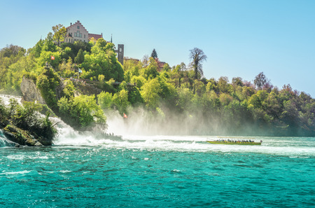 Boats toward Rhine Fall  - Boat enters the cloud of vapors made by the falling of the Rhine river, at the foot of the Laufen castle, Switzerland. Stock Photo