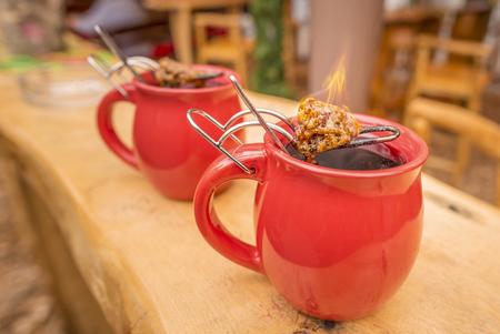 """vin chaud: boisson allemande, vin chaud et le sucre flamboyant - Image avec une tasse de vin chaud, qui a des pinces avec un cône enflammé de sucre sur le dessus. Il est une boisson traditionnelle allemande dans les foires de Noël, appelé """"Feuerzangentasse"""", ce qui signifie la Coupe du Feu. Banque d'images"""