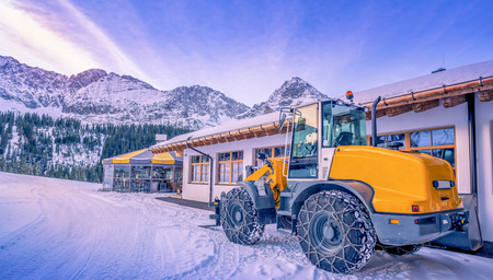 earthmover: Wheel loader winter adapted - A yellow wheel loader with chains on its tires, ready to remove the snow from the mountain paths. A lovely winter scenery from the austrian Alps