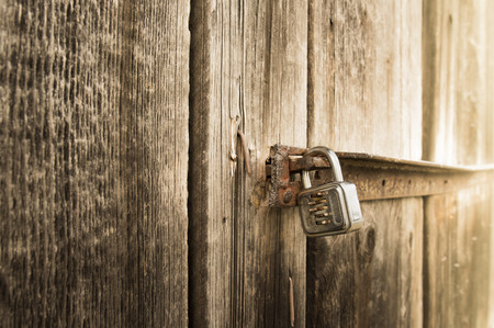 lockup: Metal lock on old barn - Close up with a metal lock on the door of an old wooden barn Stock Photo