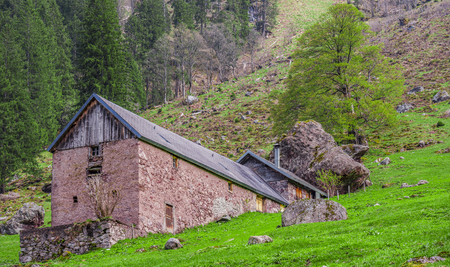 Traditional wall stone stable and house - Swiss traditional stable and house built with stone wall and shingle roof, enclosed by a huge fallen mountain rock.