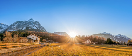 austrian village: Mountain village at the foot of the Austrian Alps - Beautiful mountain landscape with a small village, called Ehrwald, located at the foot of the Austrian Alps, under a clear blue sky and a gorgeous sun. Stock Photo