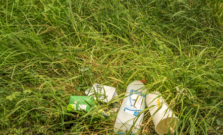 environment damage: Bunch of household trash lying on grass - Conceptual image with a heap of trash lying in nature. The grass around it is dried, yellowish, showing the damage done to the environment. Stock Photo