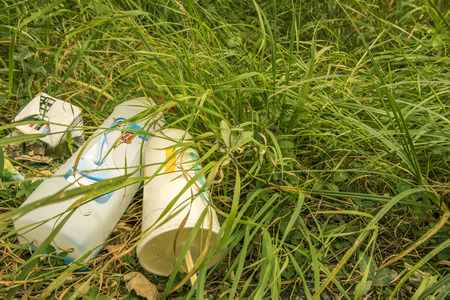 hurtful: Heap of garbage on the green grass - Environmental oriented image with a pile of trash on dried  grass, while the surrounding grass is of a beautiful green.
