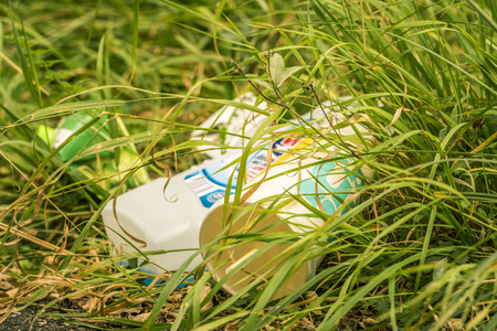 household waste: Household waste closeup in the grass - Close-up image with household garbage lying in the grass polluting the environment. Stock Photo