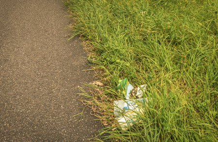hurtful: Trash on the side of the road in the grass - Pile of rubbish left on the side of the road, in grass, damaging the environment, hence a more yellow grass under the garbage.