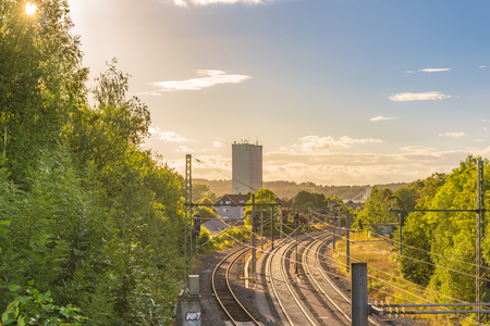 Railways under the afternoon sun - Landscape with the sun rays passing through the green trees and enlightening the railways and the industrial buildings that lies on the horizon.