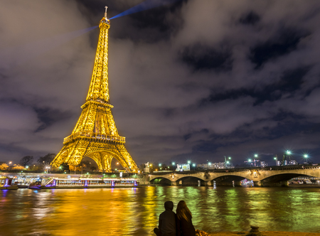 Paris, France - February 14, 2016: The Eiffel tower enlightened, the  Seine River and the silhouette of two lovers  in Paris, France on February 14, 2016.