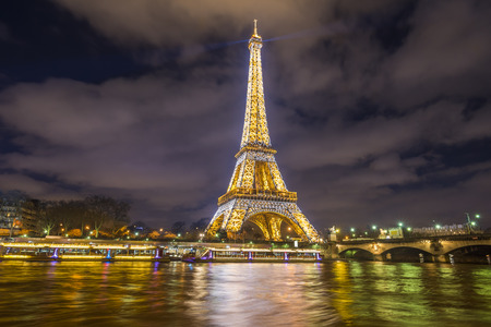 Paris, France - February 14, 2016:  The Eiffel Tower golden lights, at night, reflected in the Seine River water in Paris, France on February 14, 2016. Editorial
