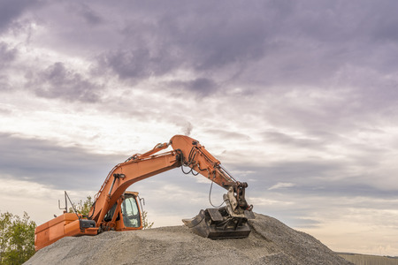 ballast: Hydraulic excavator climbed on a ballast pile - Heavy orange excavator with big bucket working on top of a ballast pile. Stock Photo