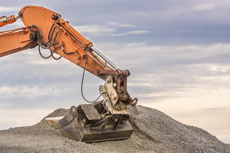 ballast: Excavator arm and bucket - Close up with the details of an orange excavator arm and bucket in a pile of ballast Stock Photo