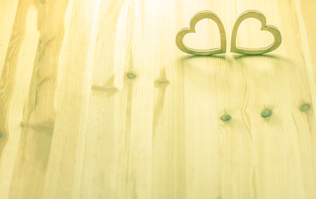 hand carved: Wooden shaped hearts - Two hearts, hand carved from wood, in a warm light on a wooden background