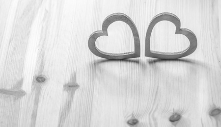 Two gray hearts on wooden table - Valentines holiday settings with two gray wooden hearts on wooden surface.