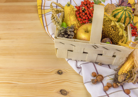 autumn arrangement: Autumn arrangement in a basket on wooden table - Lovely autumn decoration with all sorts of pumpkins, corn, grain, sunflower and forest fruits, set in a basket, on a towel and a wooden table.