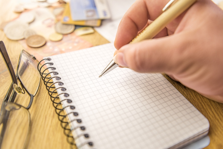 Blank notebook surrounded by financial elements - Close-up image with a blank math notebook and a mans hand holding a pen. In the background there are money, cards, bills and a pair of eyeglasses.