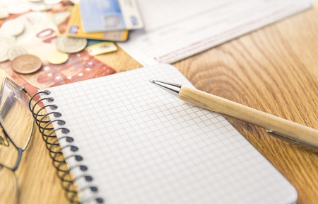 Blank notepad with pen and financial elements - Conceptual image for planing and organizing the financials with a graph notepad, pen, eyeglasses and money, cards and bills in the background.