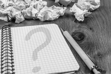 drafts: Question mark on notebook page - Graphic notebook with question mark on its page and thrown drafts on wooden desk, in monochrome settings Stock Photo