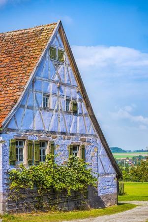 house gable: Medieval blue German traditional house  - Antique house with German specific architecture, half timbered and stone walls of blue color, windows with wooden shutters and tile gable roof.