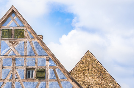 two and a half: Two german house roofs against sky - Architectural details of two lofts from medieval german houses, one with half timbered blue walls, wooden shutters and one with stone wall.