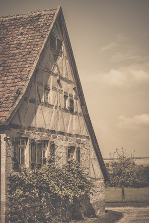 house gable: Vintage image of medieval german house - Retro style image of an antique german house with traditional architecture, gable roof, half timbered wall for the loft and stone wall, wooden shutters and vine bushes for the ground floor. Stock Photo