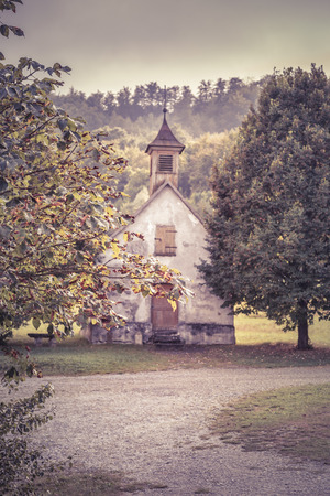 walnut tree: Autumn vintage image with an old German church in the background - Image in retro style depicting autumn at countryside with walnut tree branches in foreground and aged German church in the background.