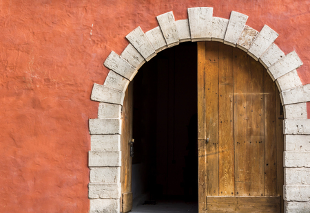 arched: Double door with one side opened - Antique arched entrance with double wooden doors, left side opened, and the orange-pink wall