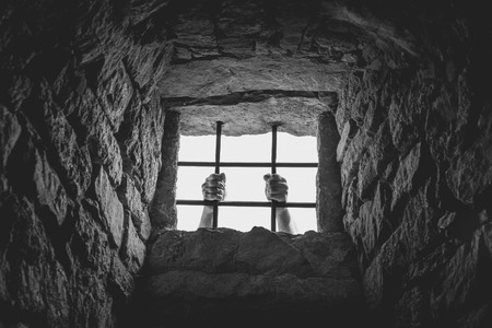 metal monochrome: Man hands behind bars - Freedom concept image, in monochrome settings, with a man holding the metal bars from a medieval german prison