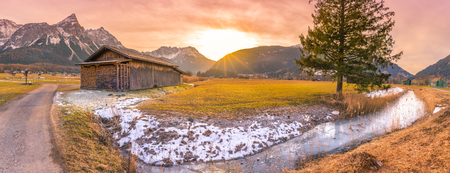 Winter sunset in the Austrian Alps - Idyllic winter scenery in a small Austrian village, with a wooden barn, a frozen river and the Alps mountains,  at dusk.