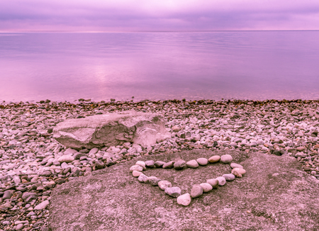 under heart: Heart shape made from stones placed on a big rock, near the lake Bodensee under a blue-purple sky, reflected in the water.