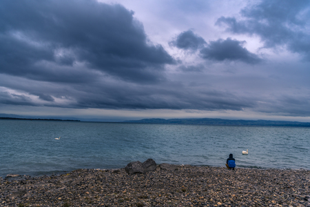 friedrichshafen: The Bodensee lake viewed from Friedrichshafen, Germany, under stormy clouds and a man sitting on its shore, thinking. Stock Photo