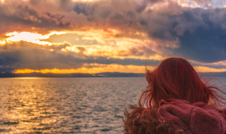 friedrichshafen: Landscape with a colorful sunset over the Bodensee lake and  a red haired woman admiring the horizon, in Friedrichshafen, Germany. Stock Photo