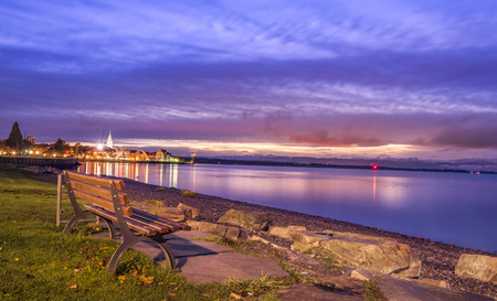 Sunrise over the lake Bodensee, with a wooden bench placed on its shore, in Friedrichshafen, Germany. Stock Photo