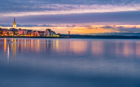 Enchanting landscape with a colorful sky reflected in the water of the Bodensee lake, as the sun is coming up, over Friedrichshafen town, Germany.