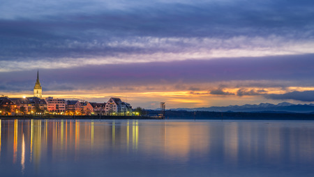 Multi-colored landscape with the Friedrichshafen town, Germany and the Bodensee lake at dawn.