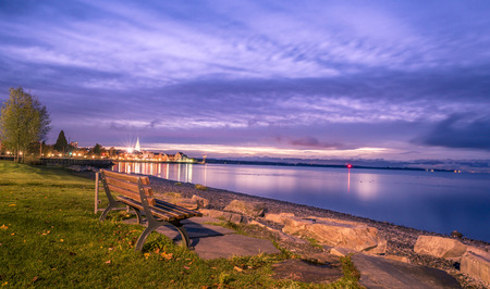 friedrichshafen: Colorful view over the Bodensee lake as the sun starts rising, with a wooden bench on its shore. Image captured in Friedrichshafen, Germany.