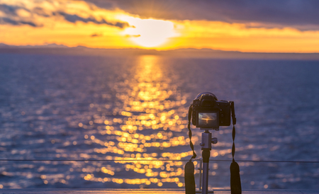 tripod mounted: A high-performance DSLR camera mounted on a tripod, while the sun is setting down over the water. Image depicting the outdoor photography.