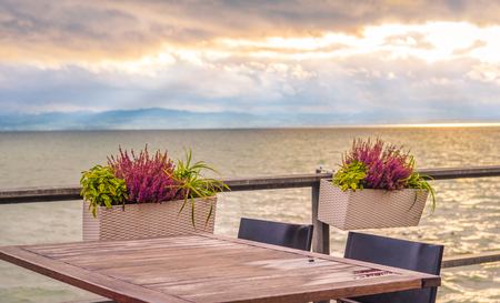 lunch table: Conceptual image with an empty table, on a terrace, on the shore of the Bodensee lake, at sunset.