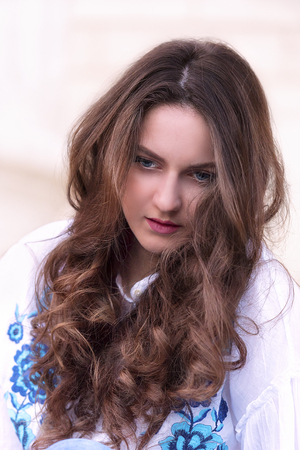 Portrait of a young caucasian girl with brown hair and blue eyes, having a meditative expression on her face.