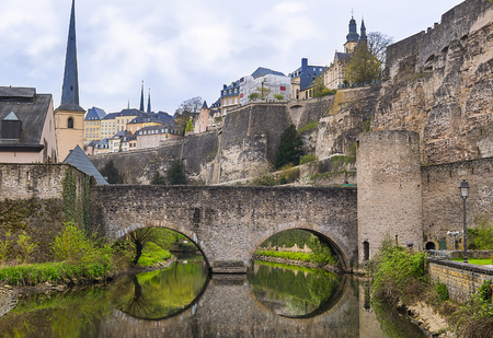 Stone bridge reflected in the water, and the ruins of a former famous castle, representing the culture and history of Luxembourg in the Middle Ages.