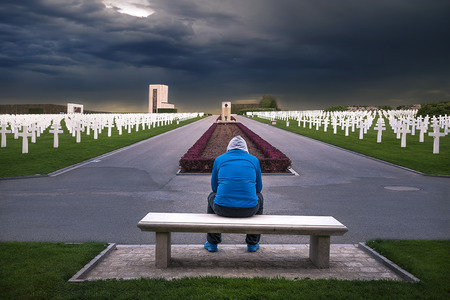 Man sitting on a bench and thinking about all the soldiers that are honored through this American memorial cemetery, located in Luxembourg. Stock Photo