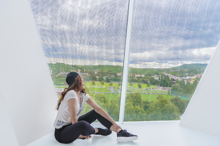 Young attractive woman, dressed in casual clothing, sits on a white floor from a modern building and looks through a very tall window. Stock Photo