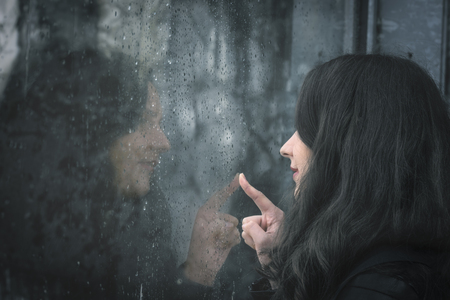 Moody image with a young woman sitting in front of a rainy window and touching it with its finger Banco de Imagens