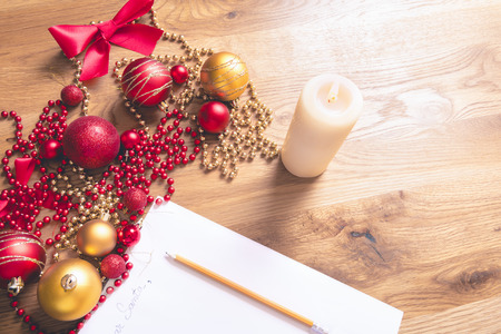 Conceptual image with a letter addressed to Santa, on a wooden table, surrounded by Christmas decorations and a lit candle. Stock Photo