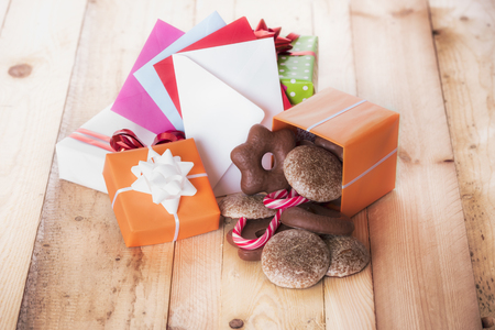 Gingerbread in a gift box near a stack of gifts and multicolored envelopes