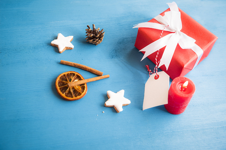 Gift, wrapped in red paper and tied with white ribbon and bow, with a blank tag attached to it, surrounded by cinnamon sticks, dried orange and star shaped cookies. Stock Photo